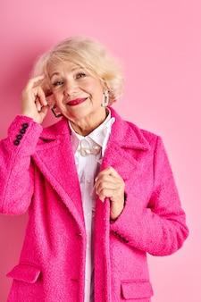 세련된 착용 수석 여자, 아름다운 회색 머리 아가씨는 멋진 옷을 입고 그녀의 나이를 즐기고, 핑크 공간 위에 고립 된 포즈를 서서