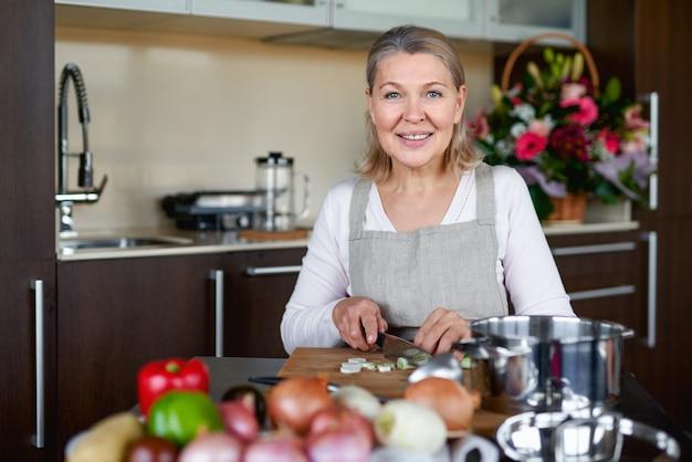 Старшая женщина на кухне готовит, смешивая еду в горшке.