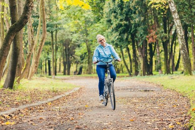 Старшая женщина в парке с велосипедом