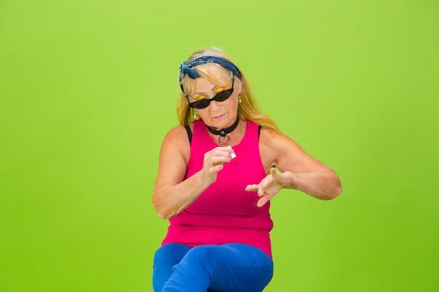 明るい緑の背景に分離された超流行の服装の年配の女性