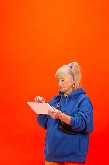 明るいオレンジ色の背景に分離された超流行の服装の年配の女性