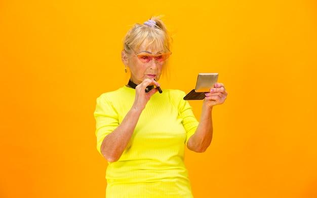 明るいオレンジ色に分離された超トレンディな服装で年配の女性