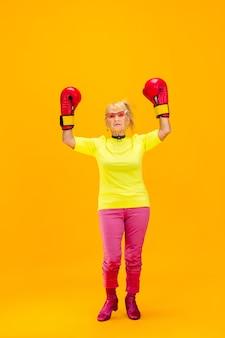 明るいオレンジ色に分離された超流行の服装の年配の女性