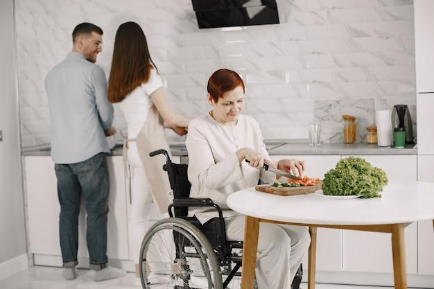 キッチンで車椅子料理の年配の女性。障害者カップルが彼女を助けています。
