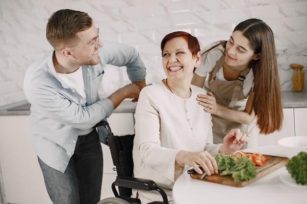 キッチンで車椅子料理の年配の女性。障害者カップルが彼女を助けています。 Premium写真