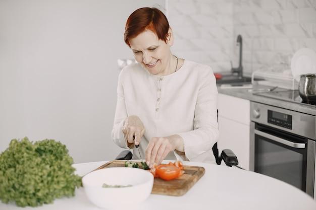 Старшая женщина в инвалидной коляске, приготовление пищи на кухне. людей с ограниченными возможностями