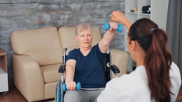 医者と一緒に家のリハビリトレーニングをしている車椅子の年配の女性。障害のある障害のある老人が専門家の助けを借りて看護師を回復し、リタイヤメントホームの治療とリハビリテーションを行う