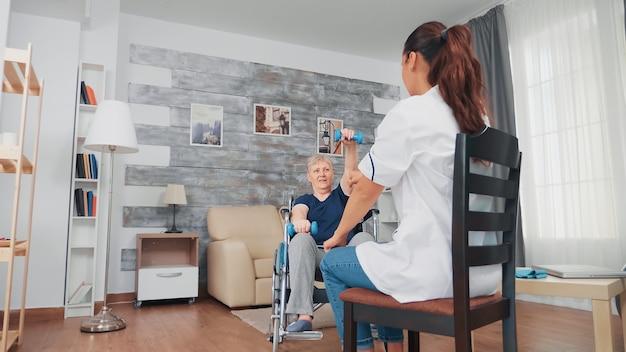 看護師と一緒に筋肉回復リハビリをしている車椅子の年配の女性。障害のある障害のある老人が専門家の助けを借りて看護師を回復し、リタイヤメントホームの治療とリハビリテーションを行う