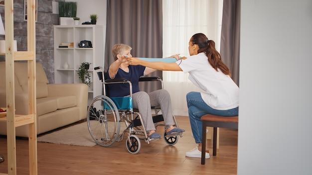 レジスタンスバンドでリハビリをしている車椅子の年配の女性。トレーニング、スポーツ、回復とリフティング、老人ホーム、ヘルスケア看護、健康サポート、社会的支援、医師と在宅