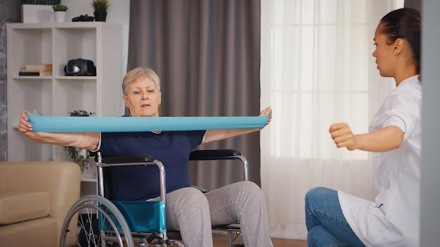 看護師の助けを借りてリハビリテーション治療を行う車椅子の年配の女性。トレーニング、スポーツ、回復とリフティング、老人ホーム、ヘルスケア看護、健康サポート、社会的支援