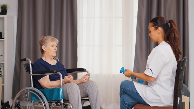 医者の助けを借りてダンベルでリハビリをしている車椅子の年配の女性。トレーニング、スポーツ、回復とリフティング、老人ホーム、ヘルスケア看護、健康サポート、社会的支援