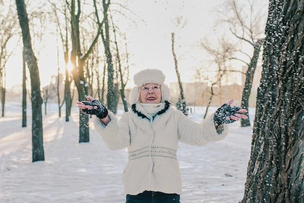 눈 공원에서 겨울을 즐기는 흰 모자와 코트에 수석 여자