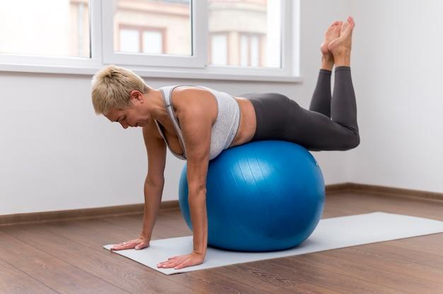 Старшая женщина в помещении делает упражнения с фитнес-мячом