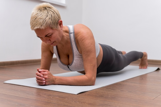 Senior woman indoors doing stretching exercises