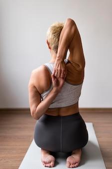Senior donna al chiuso facendo esercizi di stretching