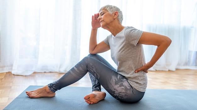 Старшая женщина травмы страдает от боли в спине из-за фитнеса.