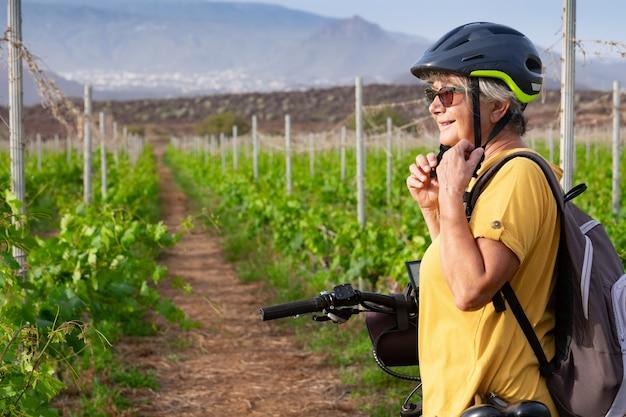 スポーツヘルメットとサングラスを身に着けて、アウトドアと自然を楽しんでいる彼女の電気自転車でブドウ園の中の年配の女性。背景の山