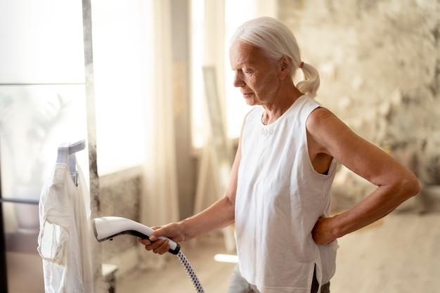 シャツにアイロンをかける年配の女性