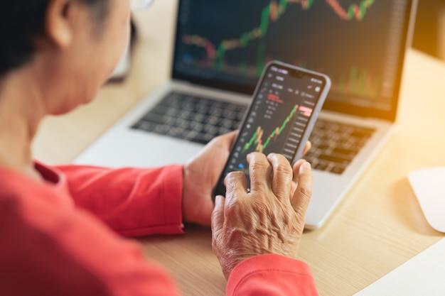 시니어 여성이 스마트폰으로 디지털 거래소에서 비트코인 가격 차트를 확인하고 있다