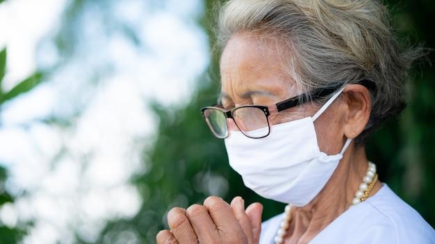 年配の女性は目を閉じて祈っていて、緑の自然の背景にフェイスマークを着用してください