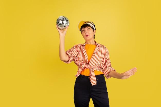 黄色の背景に分離された年配の女性。技術と楽しい高齢者のライフスタイルの概念