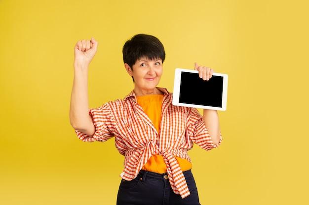 黄色に分離された年配の女性。技術と楽しい高齢者のライフスタイルの概念