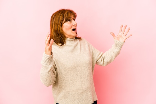 Senior woman isolated screaming to the sky, looking up, frustrated