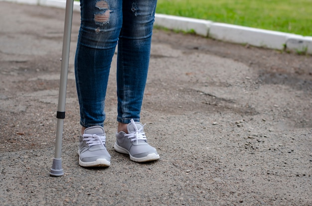 Senior woman in jeans walks with walking cane outdoors.