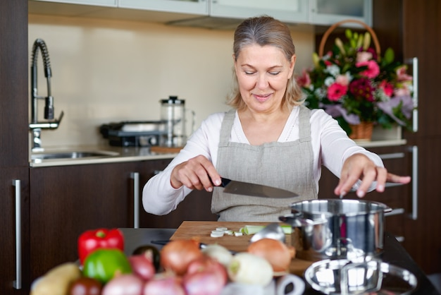 Senior woman in the kitchen cooking, mixing food in a pot