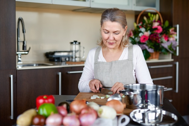 Senior woman in kitchen preparing food