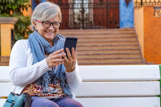 Старшая женщина смеется, забавляясь в видеозвонке со своим смартфоном, сидя на улице в городе на белой скамейке. расслабленный пожилой человек, наслаждающийся технологиями и общением