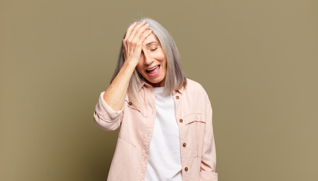 Senior woman laughing and slapping forehead like saying dã¢â€â™oh! i forgot or that was a stupid mistake