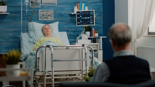 Senior woman laying in hospital bed at nursing facility