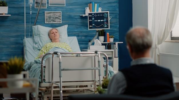 介護施設の病院のベッドに横たわっている年配の女性
