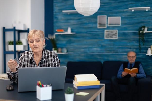 クレジットカードを使用して銀行業務を行うことを学ぶ年配の女性。自宅の居間からインターネット上で支払いトランザクションサーフィンのためにオンラインバンキングを使用しているうれしそうな年配の女性。