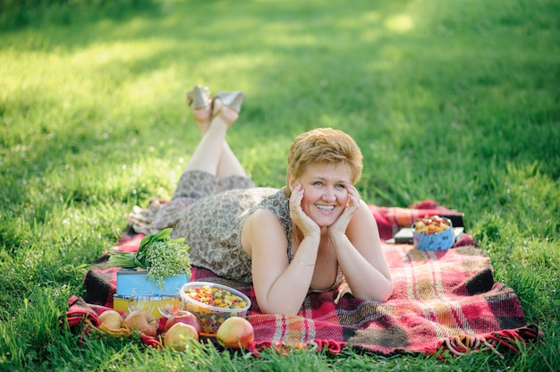 The senior woman lies belly on a plaid and poses for the camera in the park on the nature.
