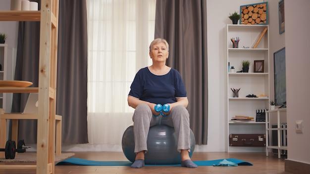 リビングルームでフィットネスボールに座ってダンベルを持ち上げる年配の女性。ウエイトダンベル活動で自宅でトレーニング健康的なライフスタイルスポーツフィットネストレーニングを持ち上げる老婆