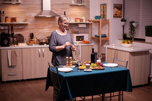 夫とのロマンチックなディナーのためにキッチンでキャンドルを灯す年配の女性。夫がロマンチックな夕食を待っている年配の女性。結婚記念日のお祝いの食事を準備する成熟した妻。