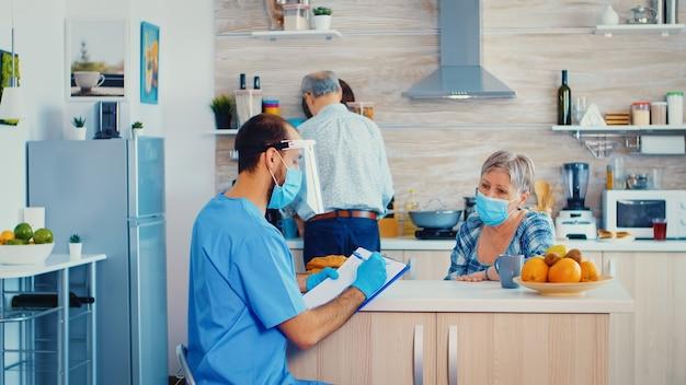 年配の女性のリスニングドクターは、家庭訪問中のコロナウイルスインフルエンザに対する保護についてどのように説明していますか。退職した年配のカップルの男性看護師ソーシャルワーカーがcovid-19の広がりを説明し、助けます