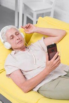 Senior woman listening music on headphone sleeping