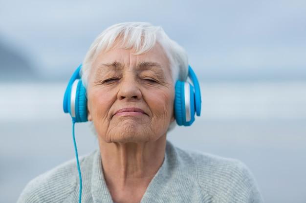 ヘッドフォンで音楽を聴く年配の女性