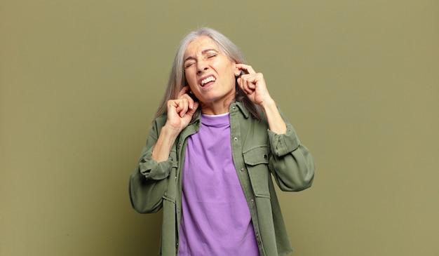 怒り、ストレス、イライラしているように見える年配の女性が、耳をつんざくような音、音、または大音量の音楽で両耳を覆っている