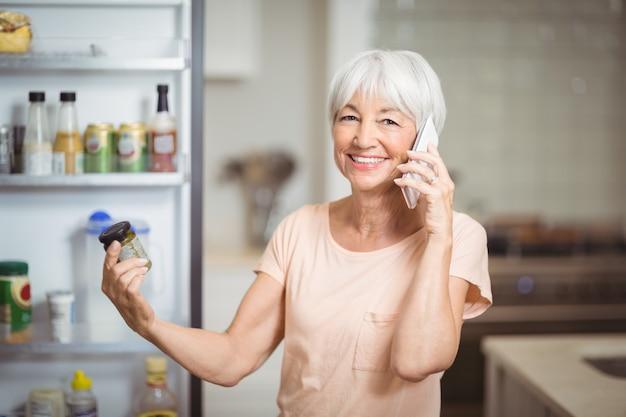 キッチンで携帯電話で話しながら瓶を見て年配の女性