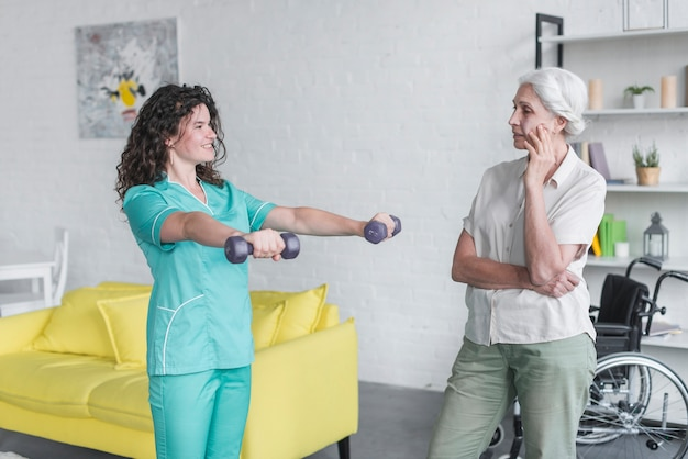 Senior woman looking at female nurse exercise with dumbbells