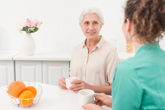 Senior woman looking at female nurse while drinking coffee