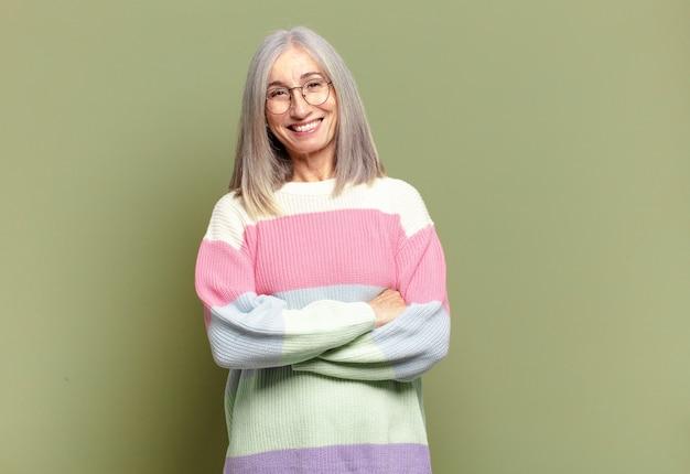 腕を組んで笑っている幸せで、誇りに思って、満足している達成者のように見える年配の女性
