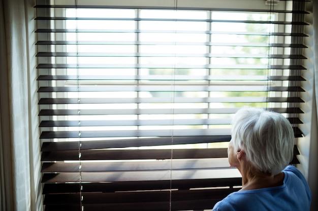 집에서 블라인드 창에서 바라 보는 고위 여자