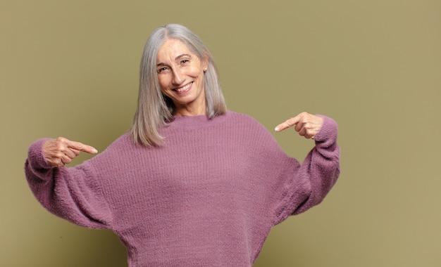 誇らしげに、傲慢で、幸せで、驚き、満足しているように見え、自己を指して、勝者のように感じている年配の女性