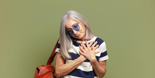 Пожилая женщина выглядит грустной, обиженной и убитой горем, держит обе руки близко к сердцу, плачет и чувствует себя подавленной