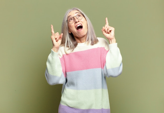 Senior woman looking shocked, amazed and open mouthed, pointing upwards with both hands to copy space